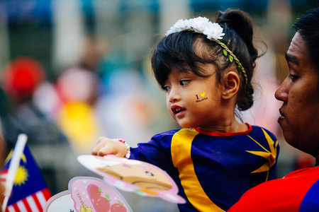 August 31st 2017, Kuala Lumpur Malaysia - A father carries his daughter to watch the National Day celebration in Dataran Merdeka Editorial