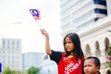 August 31st 2017, Kuala Lumpur Malaysia - A young girl waving the flag while watching the National Day celebration in Dataran Merdeka