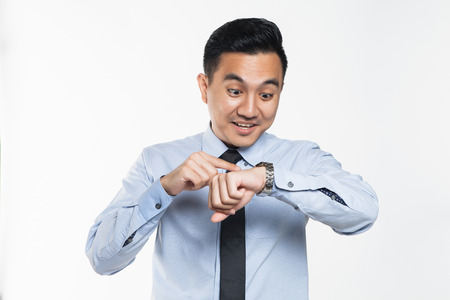 Asian man looking at his wrist watch Stock Photo