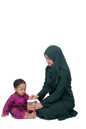 Mother giving son a cookies from food container