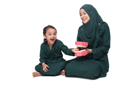 Malay mother teaching daughter on oral hygene Stock Photo - 120608397