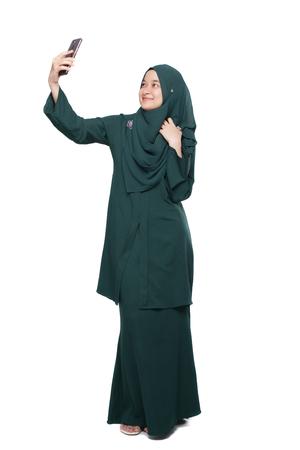 Malay woman taking selfie using smartphone Stock Photo