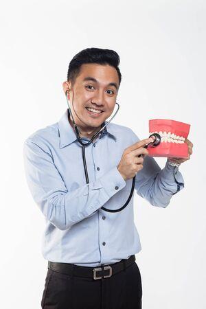 Asian man holding a stethoscope examining teeth. Stock Photo