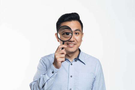 Man looking through a magnifying glass.