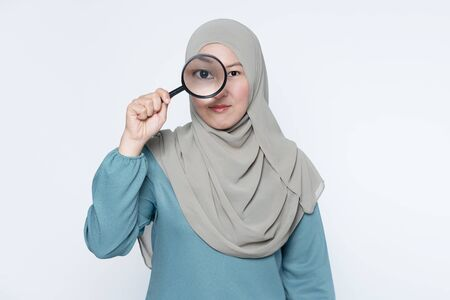 Female muslim looking through a magnifying glass.