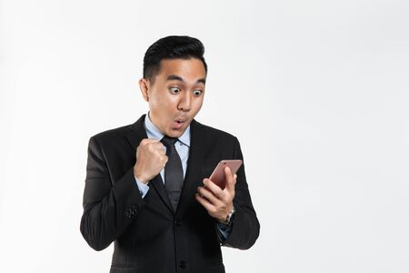 Man in suit with surprise expression while looking at his phone
