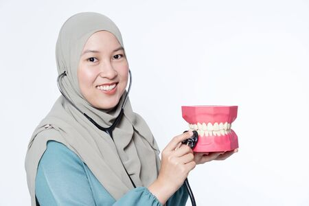 Muslim woman holding a stethoscope while inspecting a dental mould.