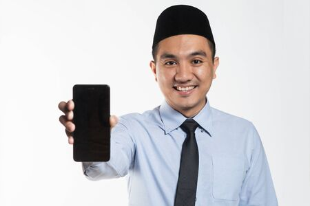 Asian male with songkok showing phone