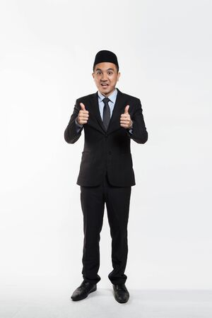 Asian business man in suit and songkok giving thumbs up