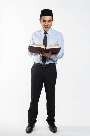 Asian male with songkok reading a book
