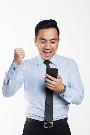 Asian man in office wear looking at his handphone with being success expression Фото со стока