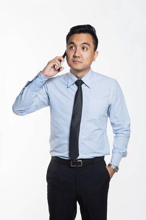 オフィスのアジア人男性は、彼の携帯電話を使用して着用 写真素材
