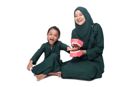 Malay mother teaching daughter on oral hygene