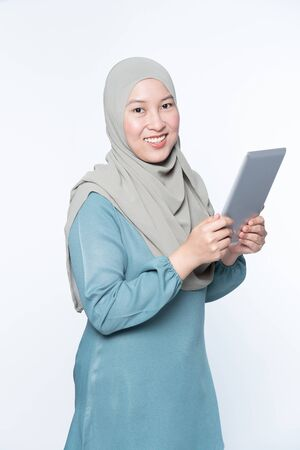 Female muslim woman using a tablet device.