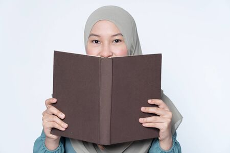 Muslim woman cover her face with hard cover book.