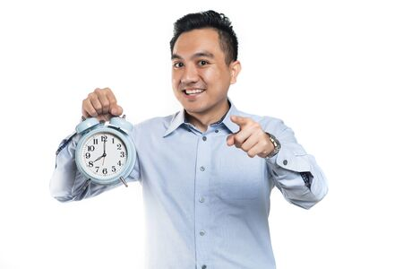 Asian man pointing while holding alarm clock Stock Photo