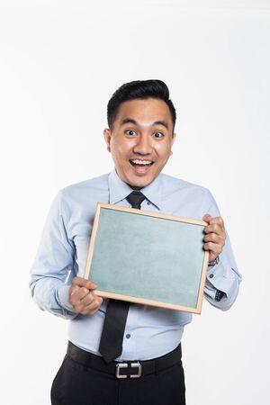 Man in office wear poiting towards a black board