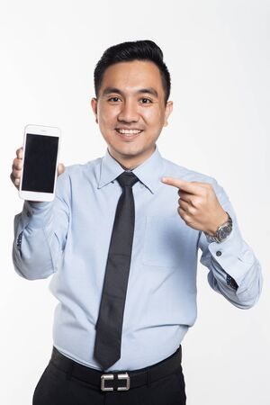 Asian man in office wear using his phone.