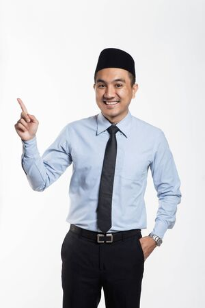 Asian business man in suit and songkok pointing his hands