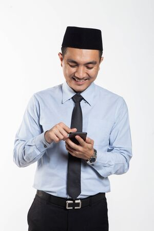 Asian male with songkok looking at his phone