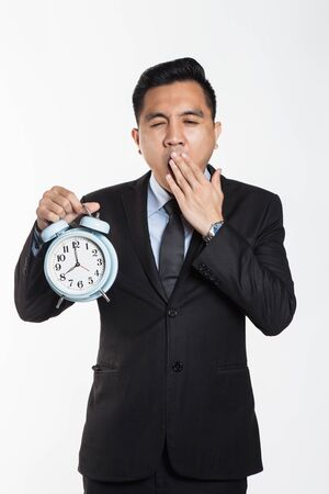 Asian business man with alarm clock with sleepy expression