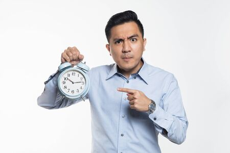 Asian man pointing at an alarm clock with angry expression