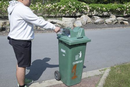 botes de basura: la botella hombre lanza de la mano en los botes de basura