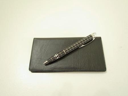 chequera: una pluma en un talonario de cheques Foto de archivo