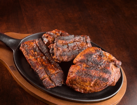 Juicy grilled steaks on a skillet with over a wooden table with copyspace photo