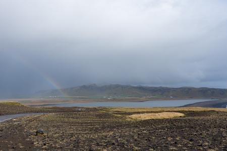 Net na de regen wees een regenboog in het meer. Helaas wilde niemand van ons duiken naar een pot met goud. Stockfoto