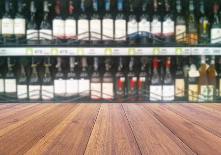 mamadera: wood floor and wine Liquor bottle on shelf - Blurred background Foto de archivo