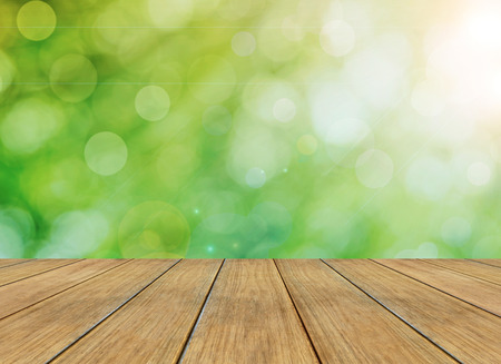 Spring or summer abstract season nature background with bokeh lights and wooden plank