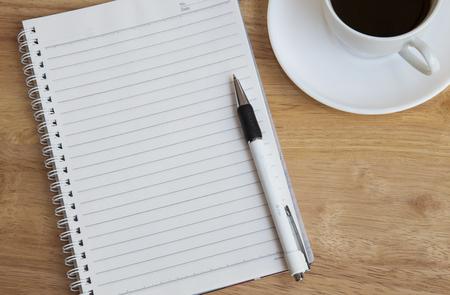 papel de notas: Bloc de notas, bol�grafo y una taza de caf� en el piso de madera Foto de archivo