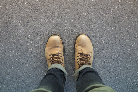 man standing on the road with jeans and boots