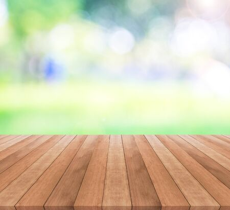 spring green: Wooden table top on blurred green background - used for display your products Stock Photo