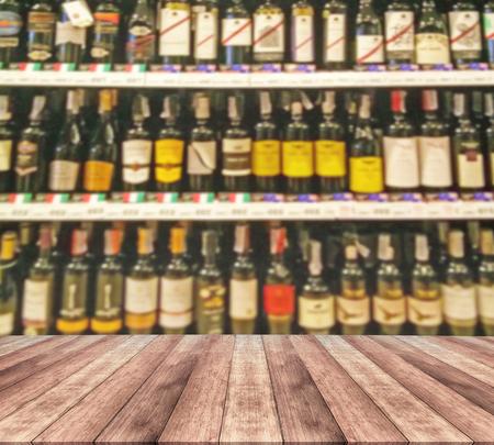 wood table top and wine Liquor bottle on shelf Stock Photo