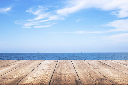 Wooden table with blue sea and beach background Stock Photo
