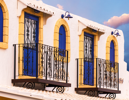 mediterranian style: House fasade with two balconies with decorative grating, blue doors and blue shutters, mediterranian style