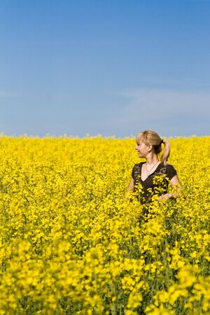 Beautiful young blonde woman in a field of wildflowers.