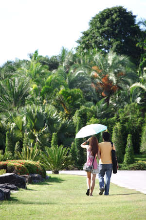View of couple a back under umbrella walking down the park. Thailand Stock Photo