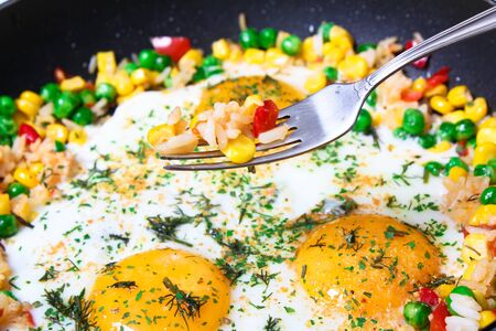 Fried eggs with vegetables, close-up