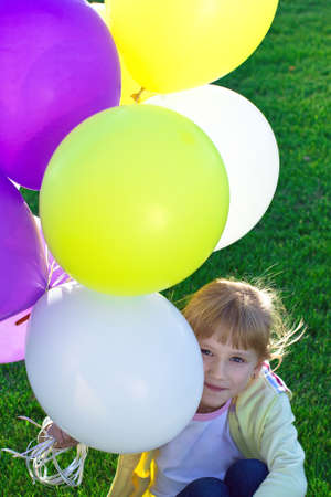 A girl sitting on the grass and holding a colorful balloons