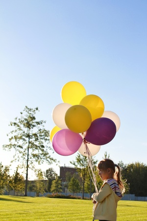 A child with multi-colored balloons in the profile. Stock Photo