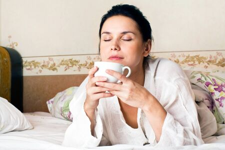 A young woman dreaming and holding white a cup of coffee on bed at bedroom Stock Photo