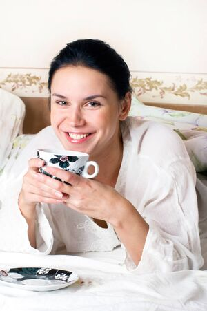 A young happy woman with a cup of coffee in the bed