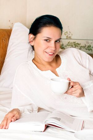 Portrait of young smiling woman with white cup and book on bed at bedroom