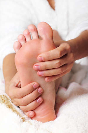 foot model: Young woman massaging his feet Stock Photo