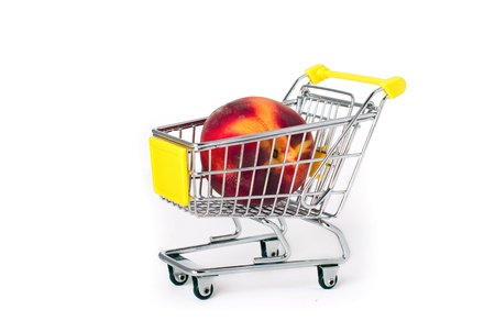 Shopping cart with a large peach on white background Stock Photo