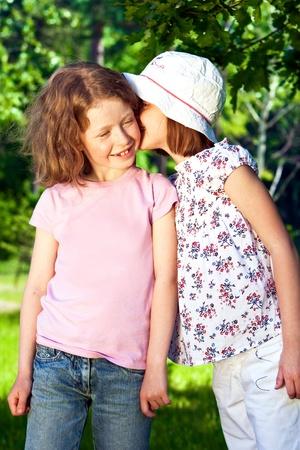 Two little whispering girls outdoors.