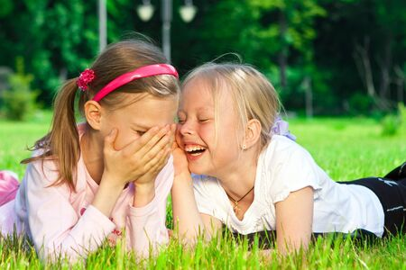 Two cute girls laughing on the green grass Stock Photo